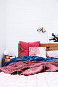 Wooden bed with cozy bed linen in red and blue against a white wall