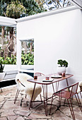 Dining set with hairpin legs and sheepskins on the terrace
