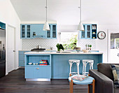 Open kitchen with blue cupboard fronts and white wall tiles