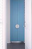 View through open door to blue cabinet door