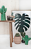 Arrangement of cacti and picture of cheese plant leaf