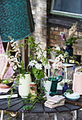 Bohemian-style flower arrangements in various vases on table