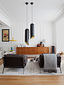 Two black couches, pendant lamps and sideboard in white living room