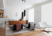 Two black couches, pendant lamps, white classic chaise and sideboard in white living room