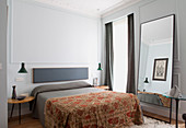 Double bed, jade-green pendant lamps above side tables and full-length mirror leaning against wall in bedroom