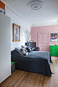 Pink wall and panelled door in bedroom of period building