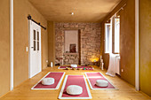 Pink yoga mats and cushions in room with mustard-yellow walls