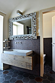 Mirror with artistic frame above concrete sink in designer bathroom with cement tiles