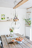 Glass pendant lamp above rustic wooden table in dining room