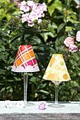 Candle lanterns made from paper lampshades on wine glasses