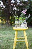 Apothekerflaschen mit Gartenblumen auf einem gelben Hocker