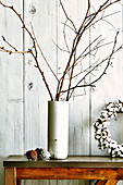 Bare branches in stone vase and pine cones as Christmas decorations