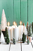 Advent arrangement: plastic mini Christmas trees and four lit candles