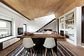 Rustic wooden table, classic chairs and fitted shelves in open-plan interior