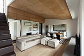 Helle Sofagarnitur in offenem Wohnraum, im Hintergrund Essbereich und Küche