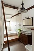 Blick ins Badezimmer mit rustikalem Waschtischmöbel und Marmor-Waschbecken