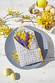 Spring flowers in folded napkin envelope decorating Easter table