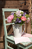 Spring bouquet of peonies, ladies' mantle and sweet peas in coffee pot on wooden chair