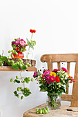 Late summer bouquets and hop vines on wooden table and chair