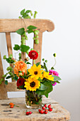 Late summer bouquet with zinnias on wooden chair