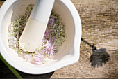 Making homemade chive-flower salt: grinding flowers and salt with mortar and pestle