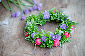 Handmade wreath of chive flowers, herbs and radishes