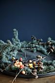 Kranz mit blauen Zedernzweigen, Zapfen und Zieräpfeln