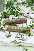 Place markers made from pieces of hazel wood decorated with purple-flowering alfalfa (Medicago sativa)