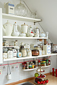 Old jugs and storage jars on kitchen shelves under sloping ceiling