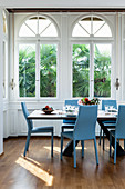 Blue chairs around dining table in window bay with arched windows