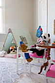 Soft toys seated at table and in tent in child's bedroom