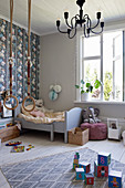 Wooden bed, gymnastic rings, soft toys and other toys in child's bedroom