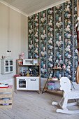 Play kitchen, shelves and rocking horse in child's bedroom with colourful wallpaper