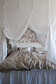 Double bed with white canopy in bedroom