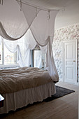 Double bed with white canopy in bedroom with vintage wallpaper