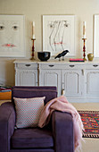 Purple armchair in front of antique sideboard in living room