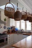 Körbe hängen über der Theke in der Landhausküche mit Oberlicht