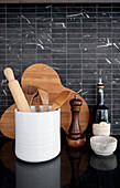 Kitchen utensils, wooden board and pepper mill against black-tiled splashback