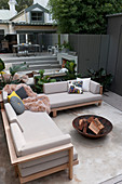 Sofa and fire bowl on terrace with mirrored wall