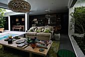 Offener Wohnraum mit Holztisch und Sofa, Zugang zur Terrasse mit Pool