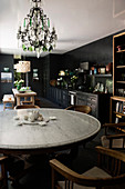 Round dining table and chairs in black kitchen