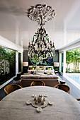 Runder Esstisch mit Stühlen in offenem Wohnraum mit Terrassenzugang