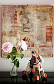 Vintage knight-and-horse toy and pink roses in front of collage