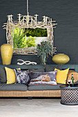 Scatter cushions with big-cat prints on wicker sofa and Bamileke side table in front of window decoratively framed with branches