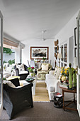 Veranda cosily furnished with various seating and roller blinds