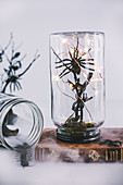 Halloween decorations handmade from jars, branches and toy spiders