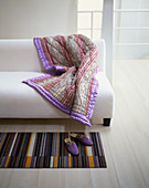 Striped quilted blanket on plain white sofa and purple slippers on striped rug