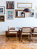 Cantilever chairs around dining table in front of pictures and mirrors on wall