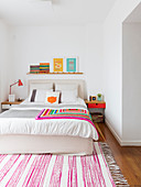 Colourful crocheted blanket on double bed and pink-and-white striped rug in white bedroom