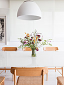 White lamp above vase of flowers on white dining table with wooden chairs